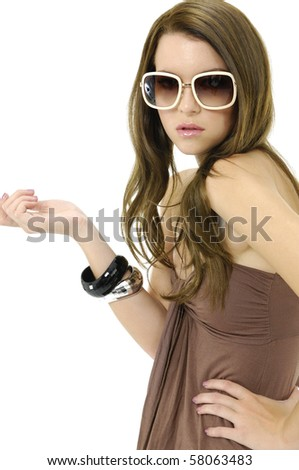 Attractive young fashion model wearing sunglasses posing in the studio - stock photo