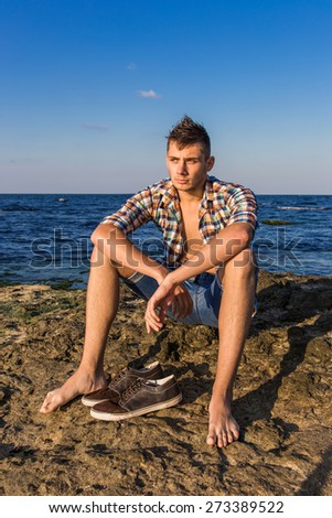 Attractive young fashion sexy man sitting on a rock near the sea water with shoes beside him - stock photo