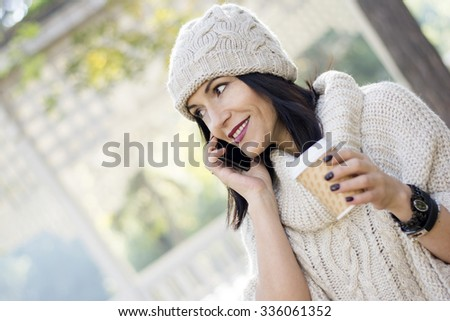 Attractive young fashionable woman with black hair using her mobile phone while enjoying fall colors in park