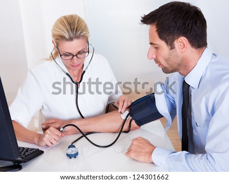 Attractive young female doctor or nurse taking a male patients blood pressure using a sphygmomanometer - stock photo