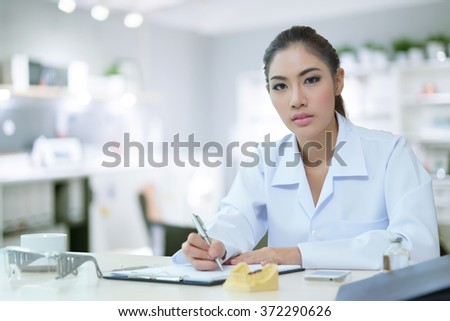 Attractive young female doctor sitting at desk in office doing paperwork.  - stock photo
