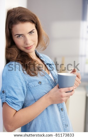 Attractive young female drinking tea at home, standing at wall.? - stock photo