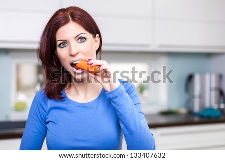 Attractive young female eating carrot in the kitchen - stock photo