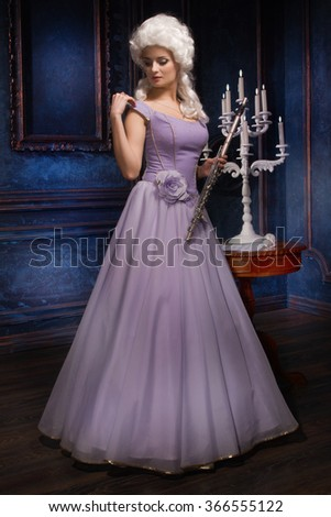 Attractive young female flautist wearing baroque dress in a luxury interior