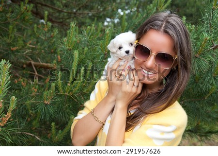 Attractive young female outside with her puppy Richon Maltiase. Shot of a beautiful brunette hugging a cute puppy. - stock photo