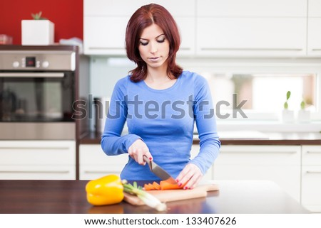 Attractive young female preparing vegetables in the kitchen
