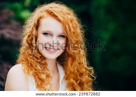 Attractive Young Female Redhead sitting up, smiling, horizontal - stock photo