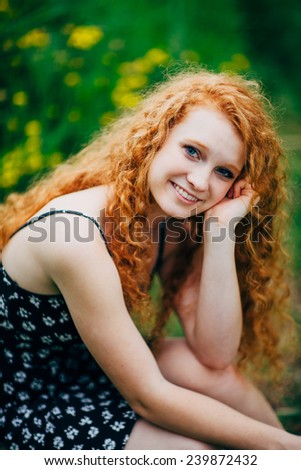 Attractive Young Female Redhead, smiling in front of flowers, leaning on cheek - stock photo