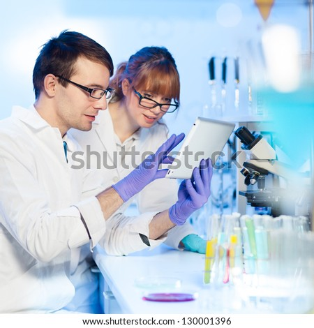 Attractive young female research scientist and her post doctoral male supervisor looking at the tablet in the life science (forensics, microbiology, biochemistry, genetics, oncology...)laboratory. - stock photo