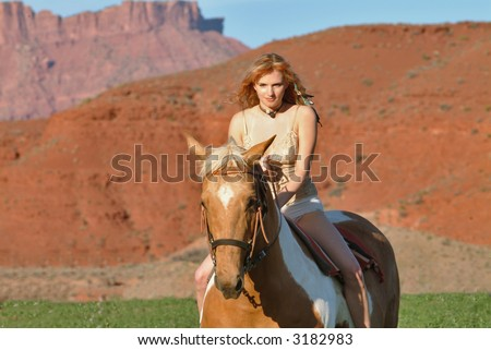 attractive young female rides horseback at dude ranch in southwest usa red rock region - stock photo