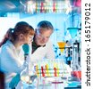 Attractive young female scientist and her senior male supervisor looking at cell colony grown in the petri dish in life science research laboratory (biochemistry, genetics, forensics, microbiology..) - stock photo