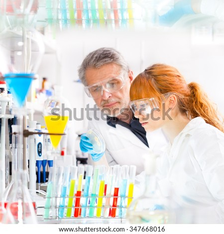 Attractive young female scientist and her senior male supervisor looking at the cell colony grown in the petri dish in the life science research laboratory - stock photo