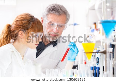 Attractive young female scientist and her senior male supervisor observing color shift of a red liquid in the glass tube in the life science research laboratory ( genetics, forensics, microbiology..) - stock photo