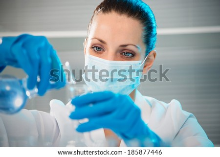 Attractive young female scientist working in laboratory - stock photo