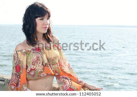 Attractive young female standing near the summer shore, horizontal shot - stock photo