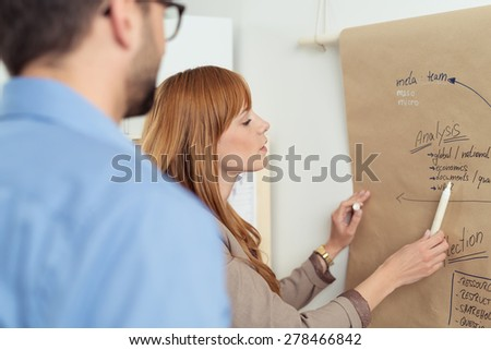 Attractive young female team leader standing discussing a project with a team member pointing to a hand-drawn planning flow chart - stock photo