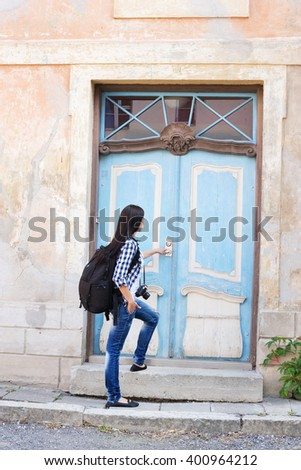 Attractive young female tourist opening door to a hostel. - stock photo