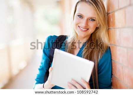 attractive young female university student using tablet computer - stock photo