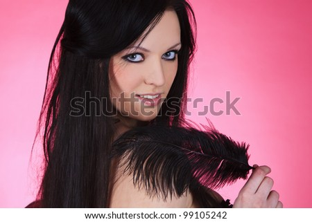 attractive young female with black feather over pink background