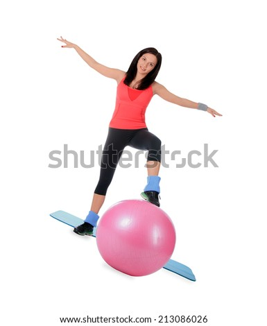 Attractive young female with fitness ball in sport center