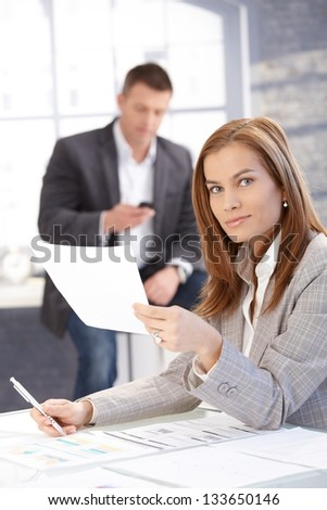 Attractive young female working at desk in bright office, man texting in background.