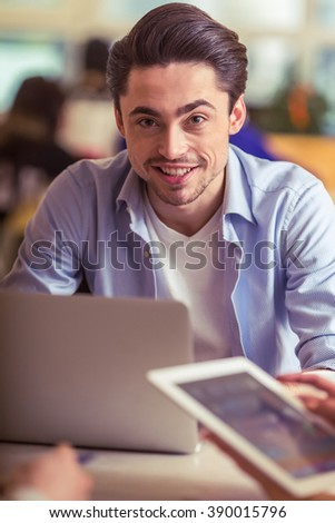 Attractive young freelancer is using a laptop and smiling while working with other people in cafe, close-up - stock photo