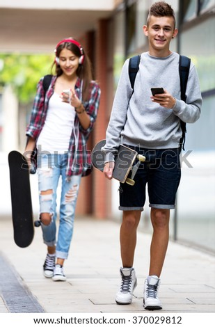 Attractive young friends carrying skateboards and walking through city - stock photo