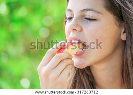 attractive young girl eating fruits isolated on green background - stock photo