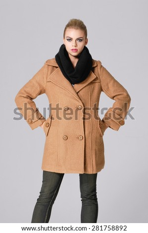 attractive young girl in coat posing	 - stock photo