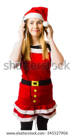 Attractive young girl listening to holiday music with headphones in santa costume. Sounds of festivity