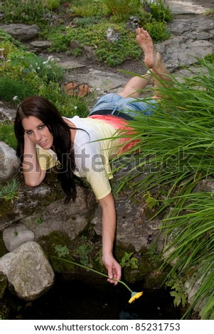 Attractive young girl plays with a pool of water in a garden