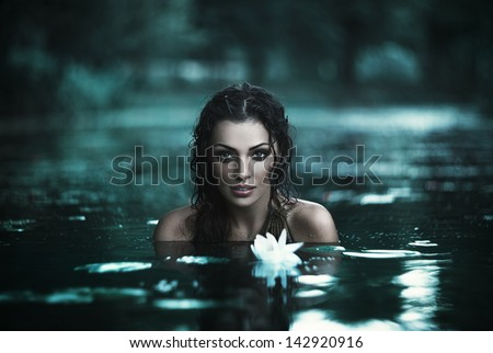 Attractive young girl posing in a river. Grain added - stock photo