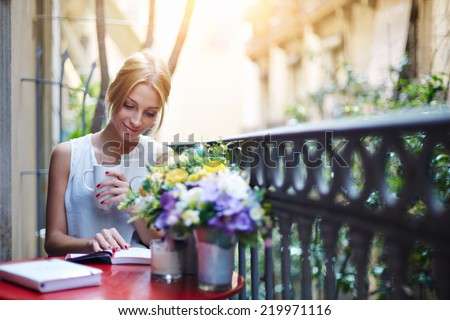 Attractive young girl reading book while drinking coffee at sunny day sitting on the balcony, beautiful young woman with cup of coffee on home balcony reading the book, female student reading book - stock photo