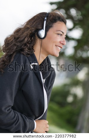Attractive young girl (20s) on profile, smiling and listening her favorite music in park. Silver headphones on ears and brown long hairs. - stock photo
