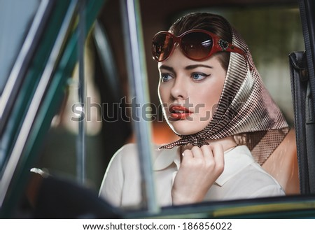 Attractive young girl sitting behind the wheel of a car - stock photo