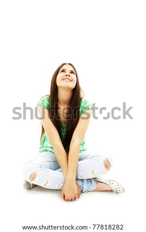Attractive young girl sitting on the floor looking up. All on white background.