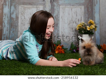 Attractive young girl smiling and feeding a bunny. - stock photo
