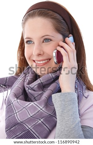 Attractive young girl talking on mobile phone, smiling, looking away. - stock photo