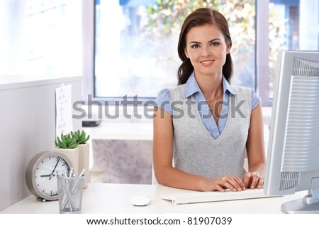 Attractive young girl using computer in bright office, smiling.? - stock photo