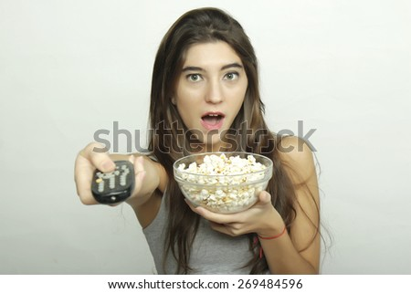 Attractive young girl watching a movie with popcorn and remote control. - stock photo