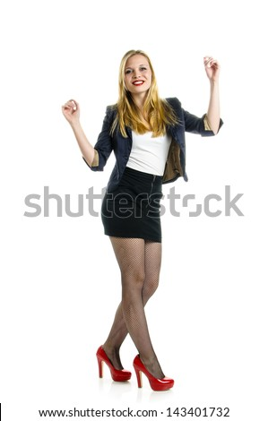 Attractive young girl wearing black miniskirt und red high heels and dancing isolated against white background.