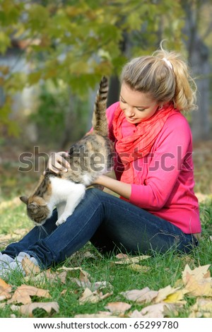 attractive young girl with cat outdoors - stock photo