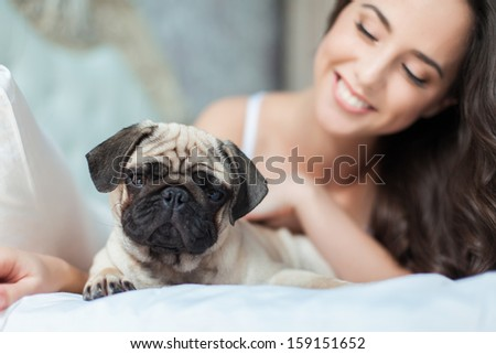 Attractive young girl with dog while laying on bed, focus on a dog