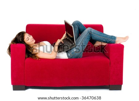 attractive young girl with laptop working on couch at home - stock photo