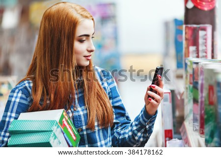 Attractive young girl with long brown hair wearing blue plaid shirt shopping at store, holding boxes and mobile phone and making photo, copy space. - stock photo