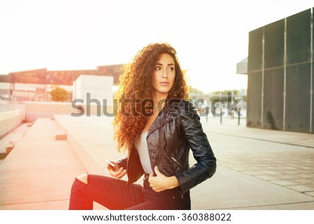 attractive young girl with long curly hair wearing a black leather jacket holding smart-phone on a city buildings background.pretty woman resting outdoors and looking away. flare light - stock photo
