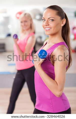 Attractive young girls are exercising with dumbbells in fitness center. They standing and smiling