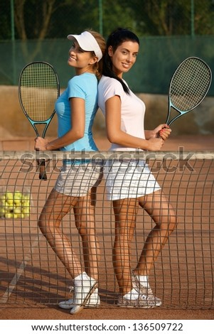 Attractive young girls posing on tennis court, smiling.