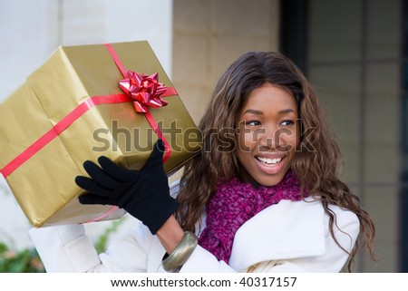 Attractive young happy African American woman walking in an urban city environment and holding a Christmas gift wrapped in gold paper. - stock photo