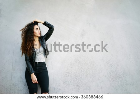 Attractive young hipster woman with long curly hair standing against street wall background and looking at the copy space area for your text message or information - stock photo